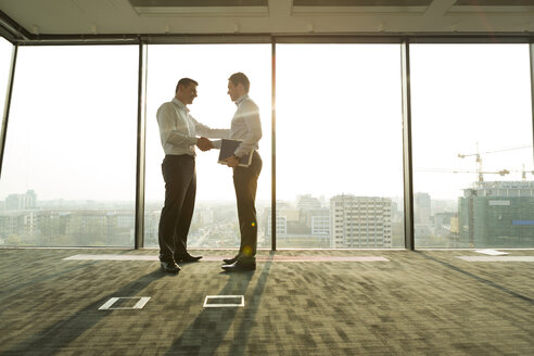 Two businessmen in sunny office shaking hands - WESTF019388