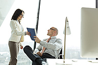 Businessman and businesswoman with documents in office - WESTF019522