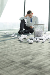 Businessman sitting on office floor surrounded by crumpled paper - WESTF019425