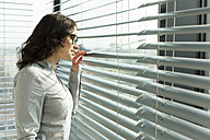 Businesswoman looking through blinds - WESTF019345