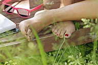 Feet of a young woman sitting on wooden bench in a garden, partial view - LAF000890