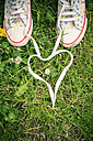 Shoelaces of two sneakers shaping heart on grass - SARF000690