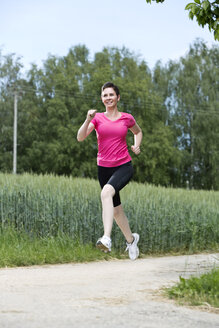 Female jogger running on field path - MAEF008379