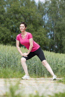 Woman making stretching exercises outside - MAEF008381