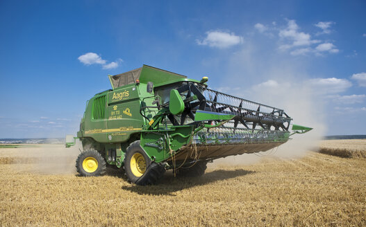 Combine harvester working on corn field - AM002342