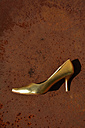 Golden stiletto on a rusty table - AXF000693