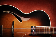 Guitar leaning against red wall - IPF000125