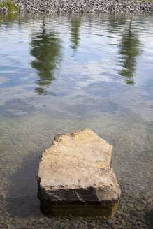 Germany, North Rhine-Westphalia, Dortmund-Hoerde, waterside of Phoenix See with stone and reflection of trees - WI000752