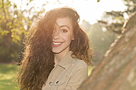 Portrait of smiling young woman with long brown hair in a park at backlight - BMA000059