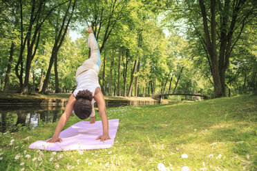 Germany, Woman exercising yoga in a park, Dog pose - VTF000277