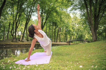 Germany, Woman exercising yoga in a park, Triangle Pose - VTF000280