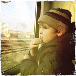 Thoughtful gesture of a three year old boy on a train. Berlin, Germany. - ZMF000294