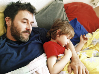 Son sleeps in his father's arm in bed, Berlin, Germany - ZMF000306