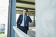 Portrait of business man telephoning with smartphone - UUF000869