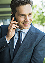 Portrait of smiling business man telephoning with smartphone - UUF000870