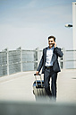 Business man with rolling suitcase telephoning with smartphone - UUF000879