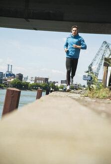 Man with headphones jogging at riverside - UUF000918