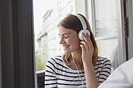 France, Paris, portrait of smiling young woman listening music with headphones - FMKF001355