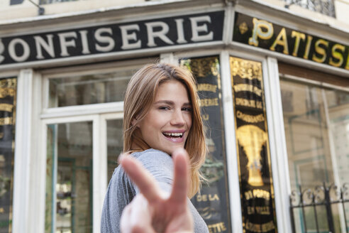 France, Paris, portrait of young woman showing victory sign in front of pastry shop - FMKF001256