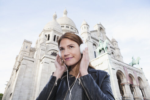 France, Paris, portrait of smiling young woman listening music with headphones in front of Sacre Coeur - FMKF001260
