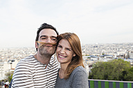 France, Paris, portrait of happy couple having fun - FMKF001263