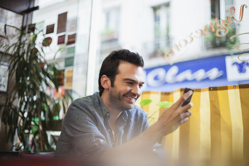France, Paris, portrait of man using his smartphone in a cafe - FMKF001277