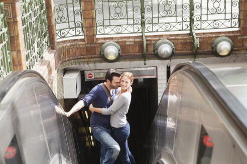 France, Paris, portrait of couple standing on escalator - FMKF001298