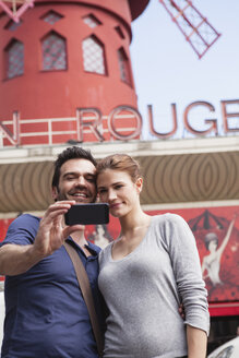 France, Paris, couple photographing  themselves with smartphone in front of  Moulin Rouge - FMK001301