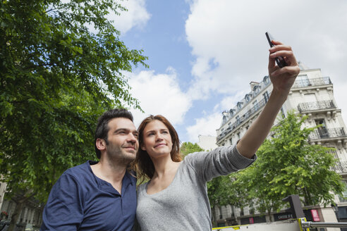 France, Paris, couple photographing  themself with smartphone - FMKF001304