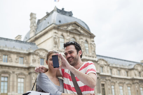 France, Paris, couple photographing  themself with smartphone - FMKF001313