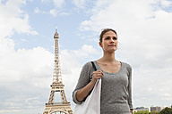 France, Paris, portrait of young woman in front of Eiffel Tower - FMKF001332