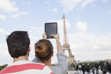 France, Paris, couple photographing  Eiffel Tower with tablet computer, back view - FMKF001335