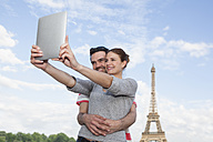 France, Paris, happy couple photographing themself with tablet computer in front of Eiffel Tower - FMKF001338