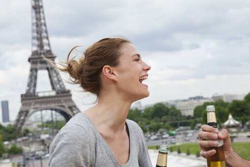 France, Paris, portrait of laughing woman in front of Eiffel Tower - FMKF001340