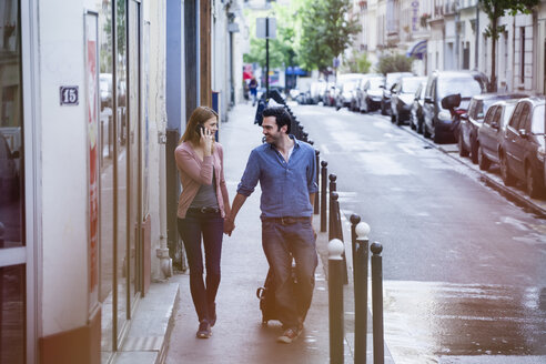 France, Paris, couple on the move with rolling suitcase - FMKF001315