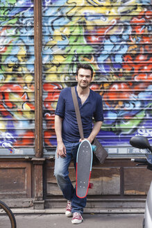 France, Paris, portrait of man with skateboard in front of graffiti - FMK001321