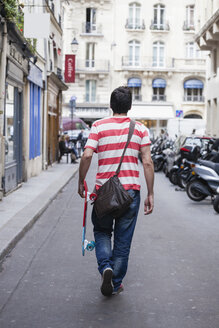 France, Paris, man with skateboard walking on a street - FMKF001324