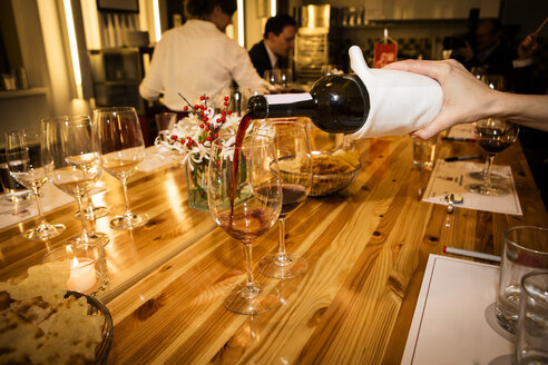 Wine is being poured into glass on laid table - SK001539