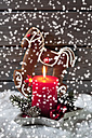 Gingerbread horse, lighted red candle and Christmas bubbles with rippling artificial snow in front - CSF021677