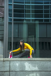 Young woman wearing yellow tracksuit top making stretching exercises - UUF000979