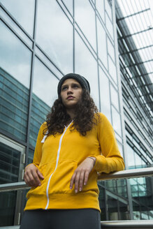 Portrait of young woman wearing yellow tracksuit top - UUF000981