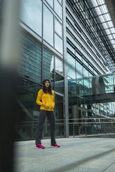 Young woman wearing yellow tracksuit top standing in front of glass front - UUF000985