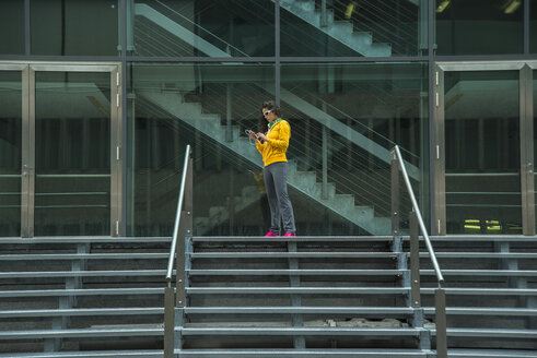 Young woman wearing yellow tracksuit top using smartphone - UUF000986