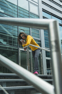 Young woman wearing yellow tracksuit top using smartphone - UUF000988