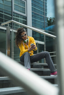 Young woman wearing yellow tracksuit top using smartphone - UUF000989