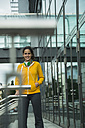 Smiling young woman wearing yellow tracksuit top - UUF000995