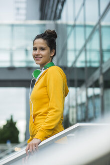 Portrait of smiling young woman wearing yellow tracksuit top - UUF000997