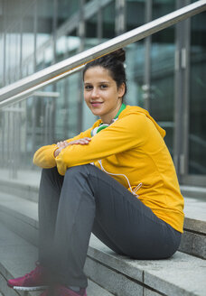 Portrait of young woman wearing yellow tracksuit top - UUF001001