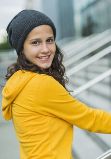 Portrait of smiling young woman wearing yellow tracksuit top and wool cap - UUF001003