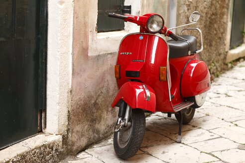 Greece, Ionic Islands, Corfu, red old Vespa scooter parking in front of house - AJ000054